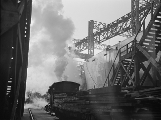 Between the ways of this large Eastern shipyard run tracks for flat cars carrying materials or sections to be hoisted onto the decks of ships under construction 2-2