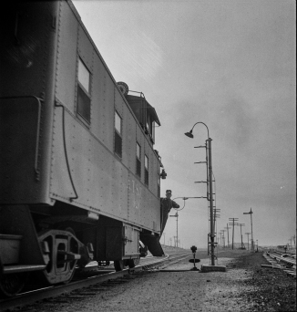 Isleta, New Mexico. Conductor of a passing freight train on the Atchison, Topeka and Santa Fe Railroad picking up a message