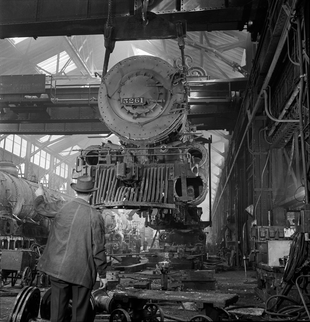 , Kansas. Lifting an engine with the eighty-ton cranes at the Atchison, Topeka, and Santa Fe Railroad locomotive shops. This locomotive will be carried to another part of the shop to be wheeled