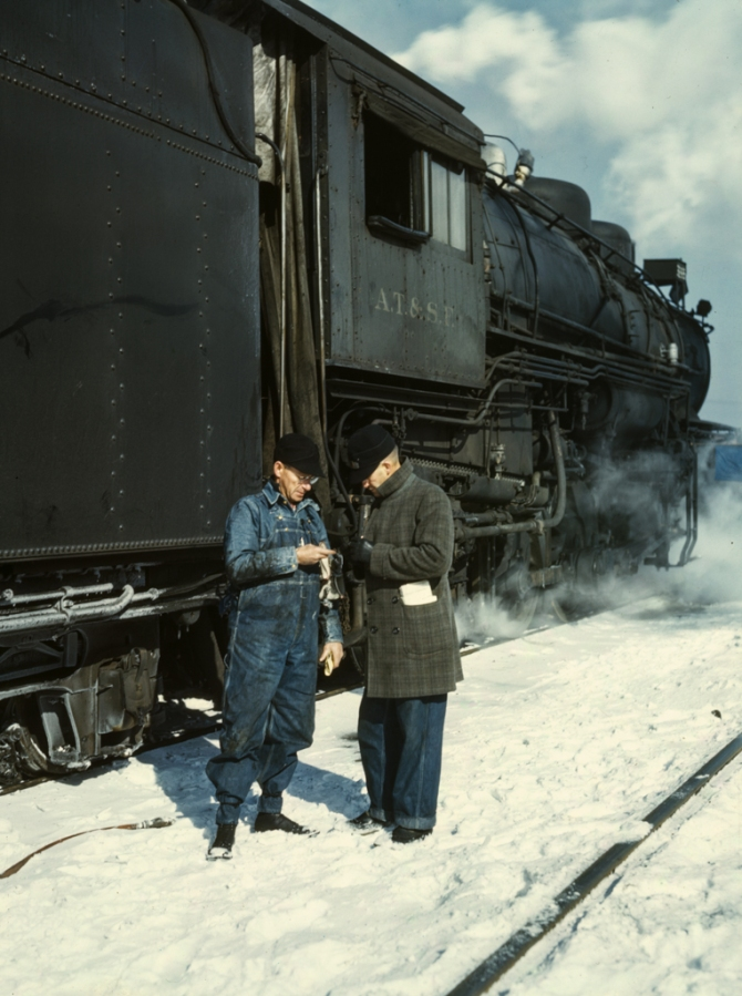Atchison, Topeka, and Santa Fe railroad conductor George E. Burton and engineer J.W. Edwards comparing time before pulling out of Corwith railroad yard for Chillicothe, Illinois; Chicago, Ill